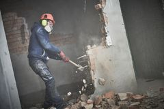 Demolition work and rearrangement. worker with sledgehammer destroying wall royalty free stock images