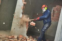 Demolition work and rearrangement. worker with sledgehammer destroying wall. Demolition work. Worker builder with sledgehammer destroying interior wall royalty free stock images