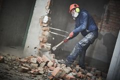 Demolition work and rearrangement. worker with sledgehammer destroying wall. Demolition work. Worker builder with sledgehammer destroying interior wall royalty free stock photos