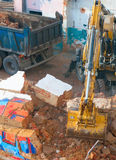 Demoliton. Digger and Truckload of Rubble in House Under Demolition Royalty Free Stock Photos