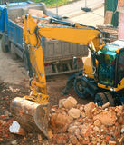 Demoliton. Digger and Truckload of Rubble in House Under Demolition Stock Photos