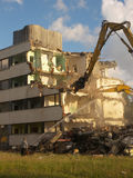Demoliton - tearing a building. Two excavators tearing a building. Intersting crops possible Royalty Free Stock Photo