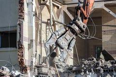 Demolizione di vecchio fabbricato industriale facendo uso delle mandibole idrauliche Fotografia Stock