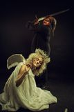 Demon and angel. Angry demon prepares to kill cute little angel by sword Stock Images