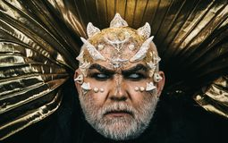 Demon die van duisternis toenemen Monster met glanzende draakhuid en doornen op gezicht over gouden metaalachtergrond, fantasie stock foto's