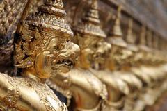 Demon gargoyles at the shrine of the Emerald Buddha, Bangkok. A row of gargoyles outside the shrine of the Emerald Buddha in Wat Po, Bangkok, Thailand Royalty Free Stock Images