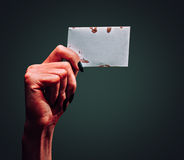 Demon hand with blank card Royalty Free Stock Photo