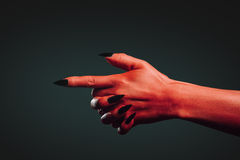 Demon hand with gesture shoot. Red demon hand with gesture shoot on dark background. Halloween or horror theme Royalty Free Stock Photos