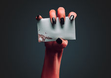 Demon hand holds empty white card Royalty Free Stock Image