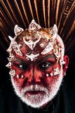 Demon head with thorns on face appearing from darkness, underworld concept. Evil monster with red skin wearing metallic. Demon head with thorns on face appearing stock photo