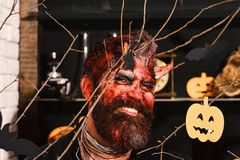 Demon with horns, evil smile and dried blood on hair. Devil or monster partying. Halloween costume party concept. Man wearing scary makeup with Halloween royalty free stock photo