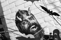 Demon with horns, evil smile face and dried blood. On hair. Devil or monster partying. Man wearing scary makeup with Halloween pumpkins and bats decor on stock image
