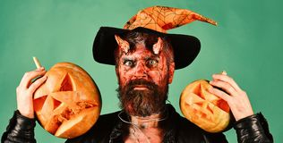 Demon with horns and scary face holds jack o lanterns. Monster with October decorations. Man wearing scary makeup and witchers hat holds pumpkins on green stock images