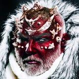 Demon met rood gezicht, scherpe doornen en wit bont over donkere achtergrond Mystiek verrukt schepsel die in eeuwig leven stock fotografie