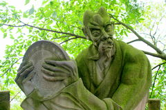 Demon statue covered in moss Stock Photos