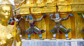 Demon supporting golden chedis, wat phra kaew, bangkok, thailand. Statues of demons supports the one of two golden chedis at the Emerald Buddha Temple royalty free stock photos