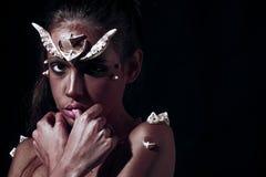 Demone con pelle rossa sopra fondo nero Creatura da inferno, concetto di orrore Ritratto della ragazza con diabolico creativo fotografia stock