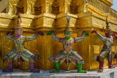 Demoner, som stöttar guld- chedi, kunglig slott Arkivbild