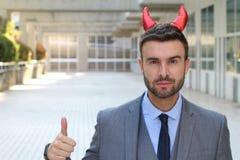 Demonic давать бизнесмена большие пальцы руки вверх стоковые изображения