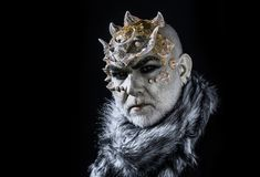 Demonic creature with thorns on head isolated on black background. King of realm of perpetual cold. Man with fictional. Make-up and white beard wearing fur royalty free stock photo