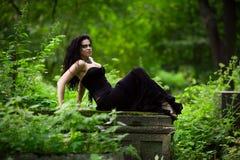 Demonic female creature. Sitting on gravestone Stock Photography