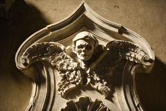 Demonic Sculpture. An eerie sculpted face peers down upon the viewer within a Catholic Basilica in Rome Italy Stock Photography