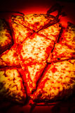 Demonic star pizza. Cursed cheese pizza sliced and diced in a rite o black magic. Demonic star pizza Stock Images