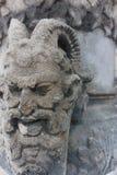 Demonio de piedra que talla la gárgola resistida cara de las ruinas imagen de archivo libre de regalías