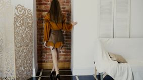 A demonstração da roupa nova no estúdio, menina na roupa na moda com composição escura elegante levanta perto da parede video estoque