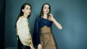 Demonstração de uma coleção nova da roupa, meninas lindos na roupa glamoroso com a composição brilhante que levanta na câmera filme