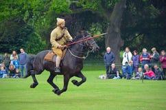 Demonstração do esporte do pegging da barraca no galope completo por um membro dos lanceiros de Punjab no uniforme da Primeira Gu Fotografia de Stock Royalty Free