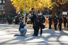 Demonstrant i i stadens centrum Portland på hans knä i mitt av en gata royaltyfria foton