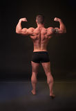 Demonstrates the strong man back muscles Stock Images