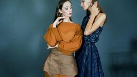 Demonstratie van een nieuwe inzameling van kleren, jonge modellen met het heldere samenstelling stellen op camera in zwarte high- stock videobeelden