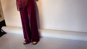 Demonstratie van manier in kunststudio Een meisjesmodel op het podium toont modieuze kleren aan stock video