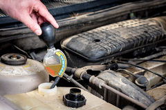 Demonstrating how to check anti freeze in an automobile Stock Image
