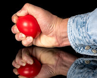 Demonstrating squeezing a red stress ball Stock Photo