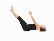 Demonstration of advanced yoga posture. Young womanshowing difficult yoga posture, full body side view, dressed in balck on white background Royalty Free Stock Image