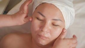 Demonstration av ändringar i den kvinnliga framsidan efter ett kosmetiskt tillvägagångssätt Händerna av en massageterapeutkosmeto lager videofilmer