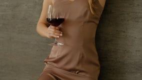 Demonstration der neuen Kleidung im Studio, M?dchen in der modischen Kleidung modern hält ein großes Glas Wein in seiner Hand stock footage