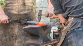 Demonstration durch zwei Schmiede bearbeiten Metall zur alten Weise lizenzfreie stockfotos