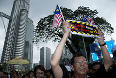 Demonstration in front of Petronas Twin Tower. KUALA LUMPUR, MALAYSIA-MAY 20: An activist holds a poster during a protest against a proposed rare earth plant to Stock Photo