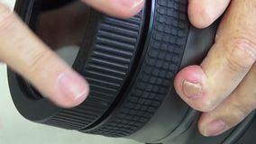 Lens cap cover tightened by a pair of hands. Demonstration of how to put on the lens cap cover of a DSLR waterproof case by twisting and tightening by hand stock video