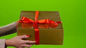 Demonstration of a large golden gift with red bow. Studio stock video footage