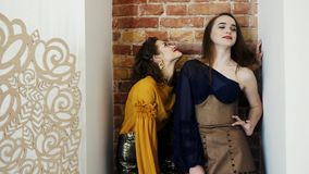 Demonstration of a new collection of clothes, professional models in luxurious clothing posing on brick wall background