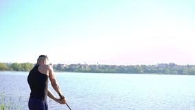 Demonstration of sword movements by master on the river background. 4k stock footage