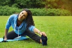 Demonstration von Übungen für das Ausdehnen in die Reinigung im Park im Sommer lizenzfreies stockfoto