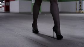 Demonstration of walking woman`s legs in black stockings, high heels in garage. Demonstration of attractive woman`s legs wearing black stockings and shoes with stock video footage