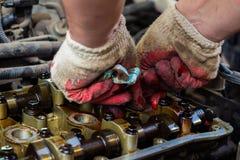 Demonteerde de interne verbrandingsmotor, maakt de hand van de hersteller de cilinderkop schoon stock afbeelding