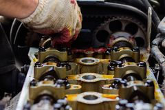 Demonteerde de interne verbrandingsmotor, maakt de hand van de hersteller de cilinderkop schoon royalty-vrije stock foto